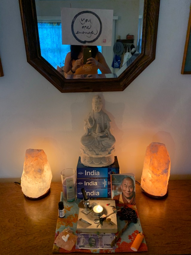 "Photograph of meditation altar with salt lamps, statue, candle, and a note that reads, ""you are enough."""