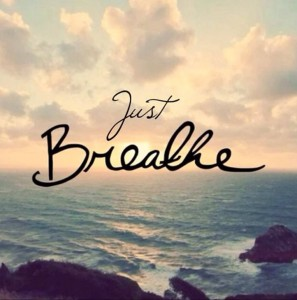 """Just Breathe"" written over landscape of ocean and sky with clouds at almost sunset."