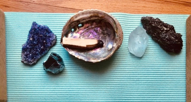 Four crystals and palo santo in a shell, all arranged on a teal yoga mat.