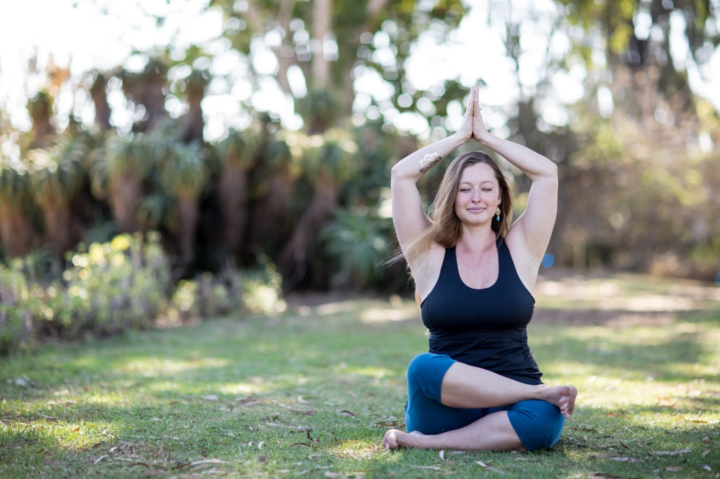 Yogini with hands in namaskar raised overhead and crossed legs sitting in a park