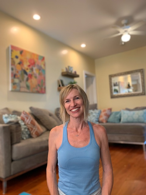 Woman with short blond hair and a large smile, wearing a blue tank top seated in her living room.