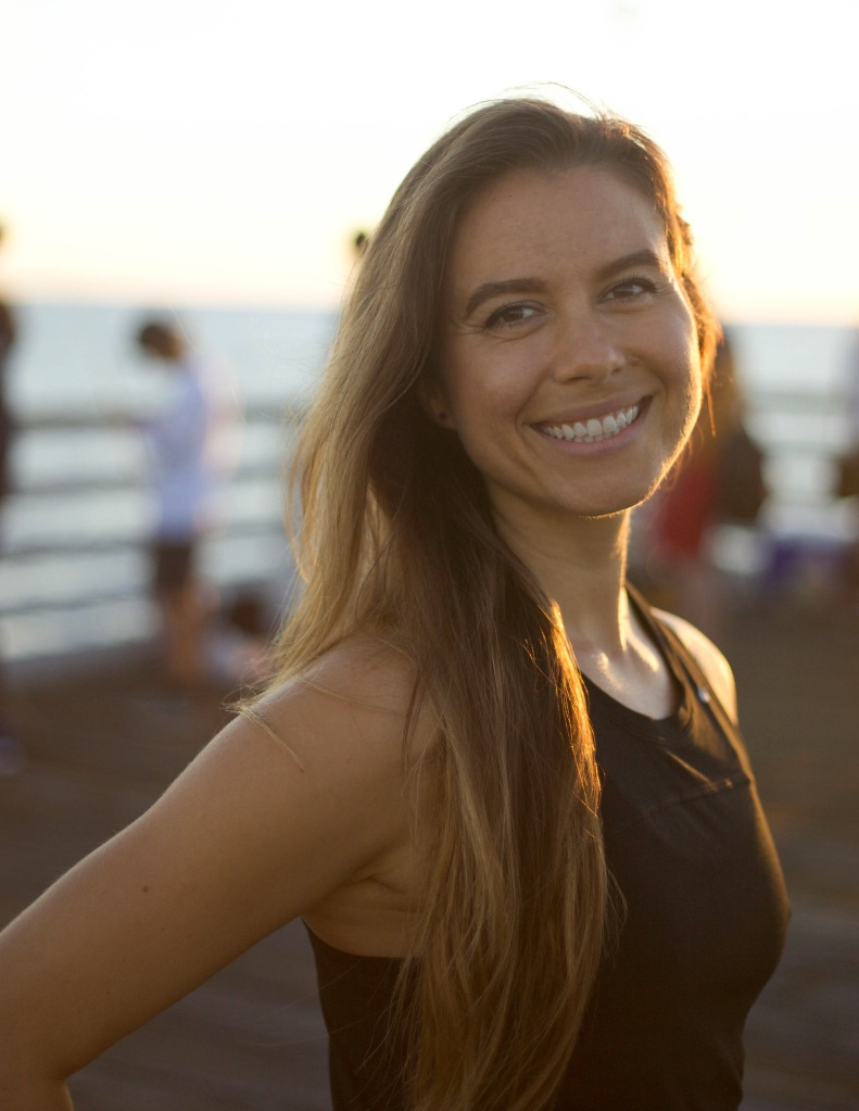 Nicole smiles towards the camera with her body tilted slightly away, her straight brown hair falls past her shoulder and she is wearing a blank tank top. Behind her is a blurred scene of a jetty and the ocean.